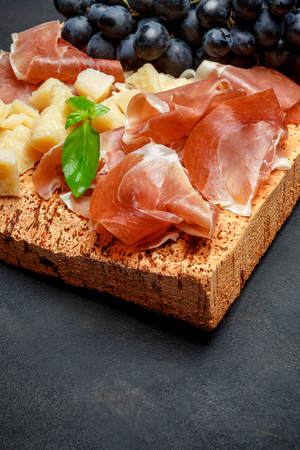 italian food with grapes, prosciutto and cheese on cork cutting board Imagens - 97360885