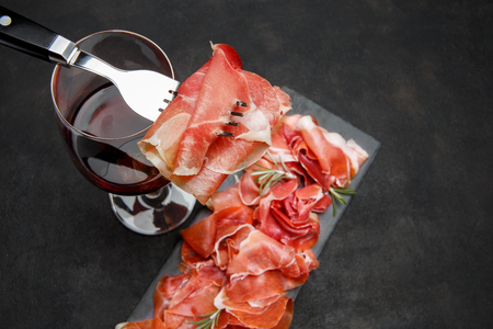 Italian prosciutto crudo or spanish jamon anw glass of wine