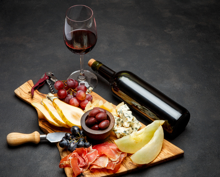 Meat plate antipasti snack - Prosciutto ham, blue cheese, melon, grapes, Olives Stock Photo