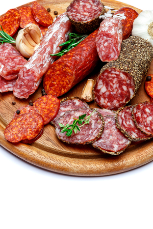 Various types of Dried organic salami sausage on wooden cutting board Фото со стока