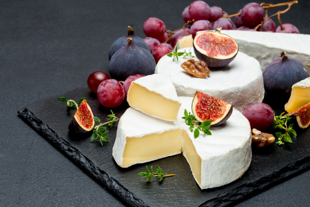 Camembert cheese and cut a slice on stone serving board