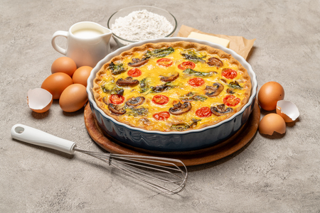Baked homemade quiche pie in ceramic baking form, eggs and cream