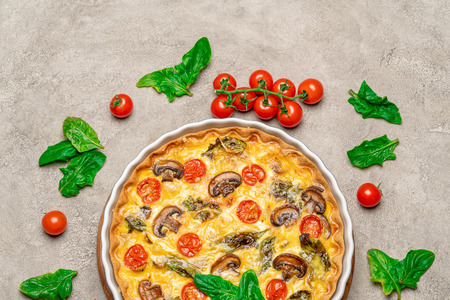 Baked homemade quiche pie in ceramic baking form on concrete background Stock Photo