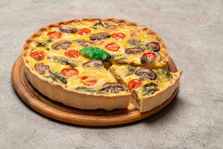 Traditional french Baked homemade quiche pie on wooden cutting board