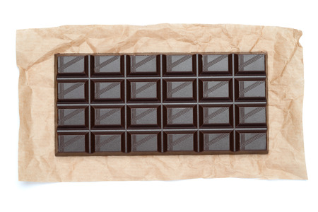 dark chocolate bar on craft packaging paper isolated on white background with clipping path
