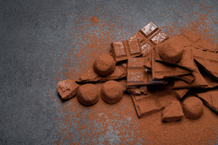 Dark or milk organic chocolate pieces, cocoa powder and truffle candies on dark concrete backgound