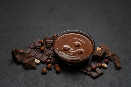 glass bowl of chocolate cream or melted chocolate, pieces of chocolate and hazelnuts on dark concrete background