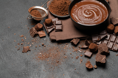 ceramic bowl of chocolate cream or melted chocolate and pieces of chocolate isolated on dark concrete background
