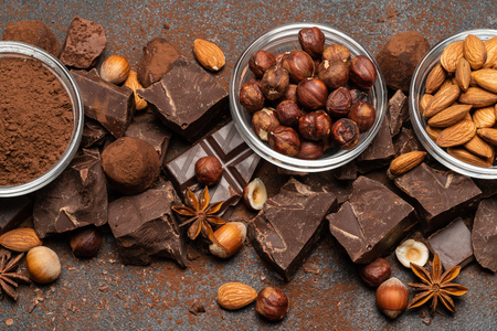 Heap of broken chocolate pieces and nuts on dark concrete background 免版税图像