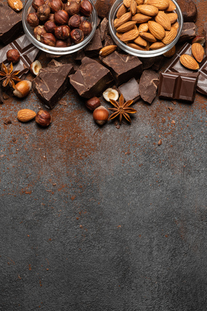 Heap of broken chocolate pieces and nuts on dark concrete background 版權商用圖片