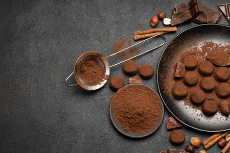 Chocolate truffles candies and cocoa powder on dark concrete background Banco de Imagens