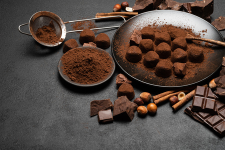 Chocolate truffles candies and cocoa powder on dark concrete background Archivio Fotografico