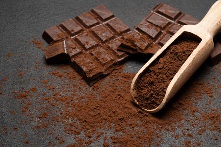 Dark Chocolate chunks and cocoa powder in wooden scoop on dark concrete background Reklamní fotografie - 121466406