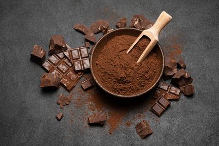 Dunkle Schokoladenstücke und Kakaopulver in Holzschaufel auf dunklem Betonhintergrund