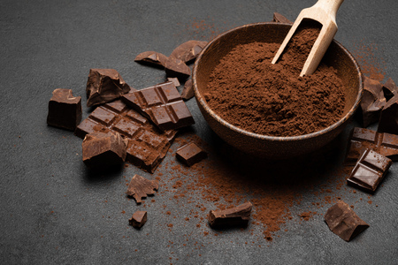 Dark Chocolate chunks and cocoa powder in wooden scoop on dark concrete background