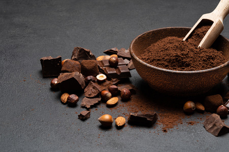 Dark Chocolate chunks, nuts and cocoa powder in wooden bowl on dark concrete background Reklamní fotografie - 121466422