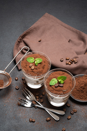 two portions Classic tiramisu dessert in a glass on dark concrete background