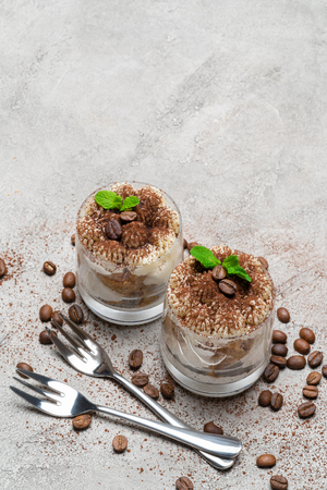two portions Classic tiramisu dessert in a glass on concrete background