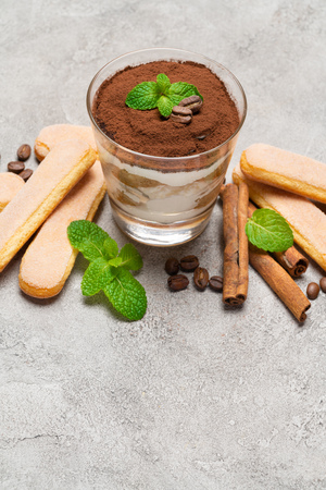 Classic tiramisu dessert in a glass and savoiardi cookies on concrete background Stock fotó