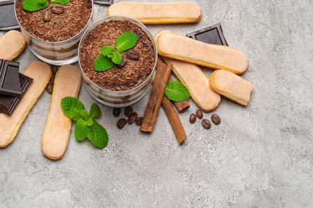 Classic tiramisu dessert in a glass and savoiardi cookies on concrete background Stok Fotoğraf