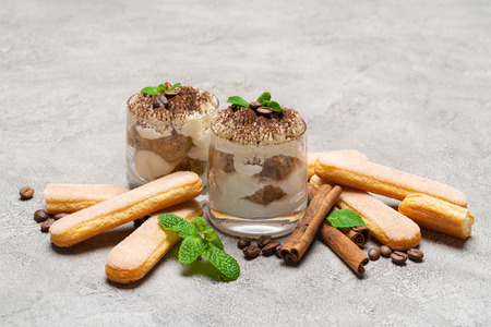 Classic tiramisu dessert in a glass and savoiardi cookies on concrete background 写真素材
