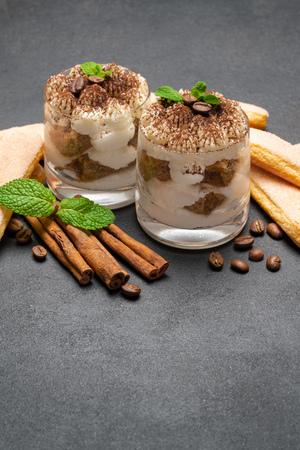 Classic tiramisu dessert in a glass and savoiardi cookies on dark concrete background