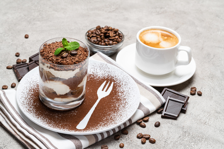 Classic tiramisu dessert in a glass and cup of coffee on concrete background