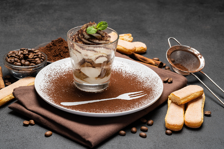 Classic tiramisu dessert in a glass and cup of coffee on dark concrete background