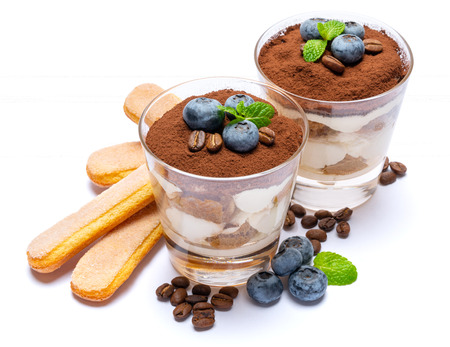 Classic tiramisu dessert with blueberries in a glass isolated on a white background