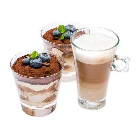 Klasyczny deser tiramisu z jagodami w szklance i filiżance kawy na białym tle ze ścieżką przycinającą