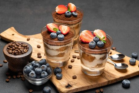 Classic tiramisu dessert with blueberries and strawberries in a glass on dark concrete background Imagens
