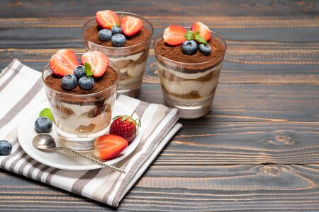 Classic tiramisu dessert with blueberries and strawberries in a glass on wooden background