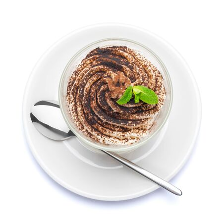 Classic tiramisu dessert in a glass on plate with spoon isolated on a white with clipping path