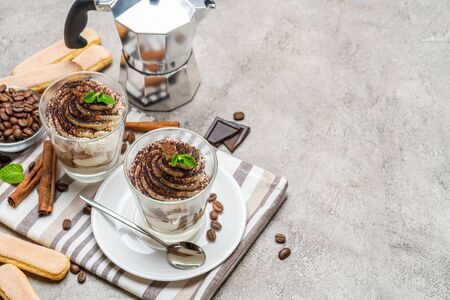 Classic tiramisu dessert in a glass and coffee makeron concrete background