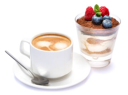 Cup of cofee and Classic tiramisu dessert with blueberries and raspberries in a glass isolated on a white background with clipping path 免版税图像