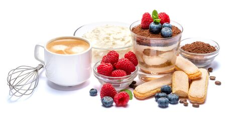 Classic tiramisu dessert with blueberries and raspberries in a glass, savoiardi and mascarpone cheese isolated on a white with clipping path