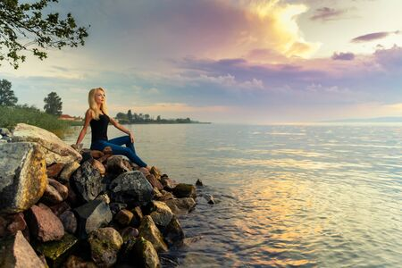 Beautiful young woman sits on the rocks by the Balaton lake