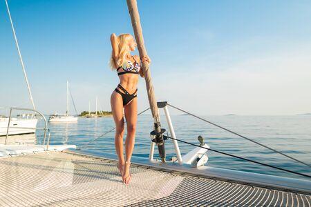bella donna in costume da bagno che si rilassa sul fronte di uno yacht?