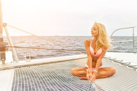 Beautiful young sexy blonde girl in a swim suit on a yacht holding glass of wine at sunny summer day. Croatia. Europe Imagens - 127327605