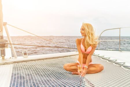 Beautiful young sexy blonde girl in a swim suit on a yacht holding glass of wine at sunny summer day. Croatia. Europe Imagens