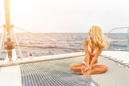 Beautiful young sexy blonde girl in a swim suit on a yacht holding glass of wine at sunny summer day. Croatia. Europe Imagens - 127332433