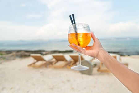 Woman holding Delicious classic iced   cocktail with ice cubes on a hot tropical beach in summer sunshine