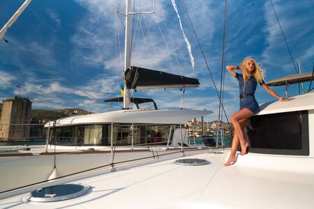 beautiful young woman in casual wear standing on a yacht fore at Trogir marina, Croatia Stock Photo