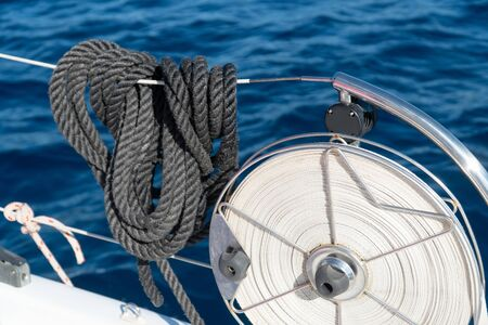 black mooring lines hanging on the reeling on a sailing yacht