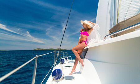 schöne Frau in Badebekleidung entspannt auf einer Yacht