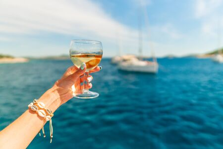Woman holding glass of white wine over ocean background with yacht on background