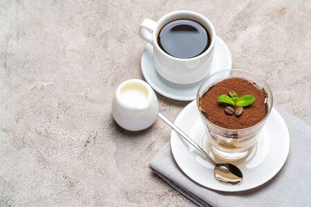 Classic tiramisu dessert in a glass, cup of espresso coffeeand cream on concrete background Reklamní fotografie - 128693858
