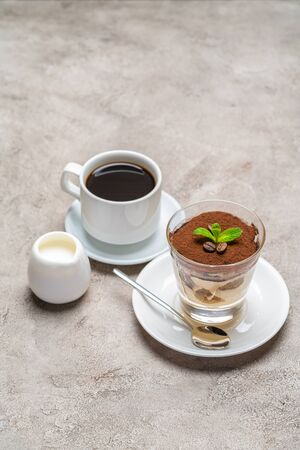 Classic tiramisu dessert in a glass, cup of espresso coffeeand cream on concrete background Reklamní fotografie