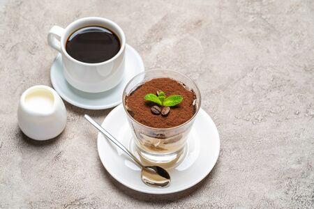 Classic tiramisu dessert in a glass, cup of espresso coffeeand cream on concrete background Reklamní fotografie - 128694046