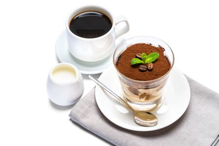 Classic tiramisu dessert in a glass, cup of espresso coffee and cream isolated on white background